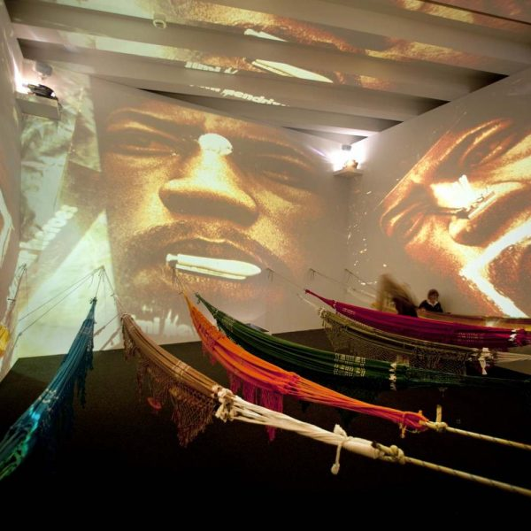 colorful fabrics stretched across room with projection of man's face