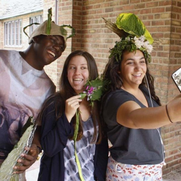 three students pose with plant headdresses