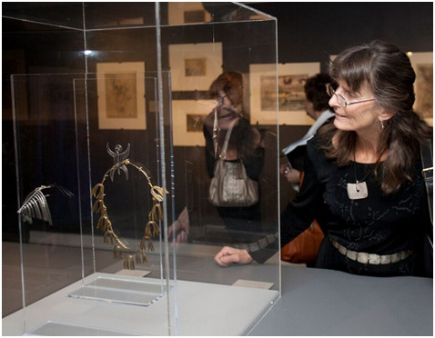 woman looks at necklace in display case