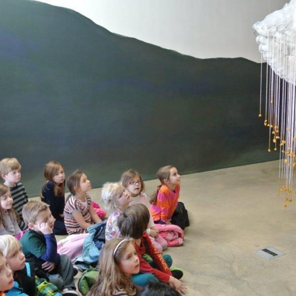 children look up at hanging sculpture