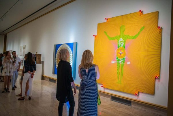 two women observe large neon painting of human figure with Buddha