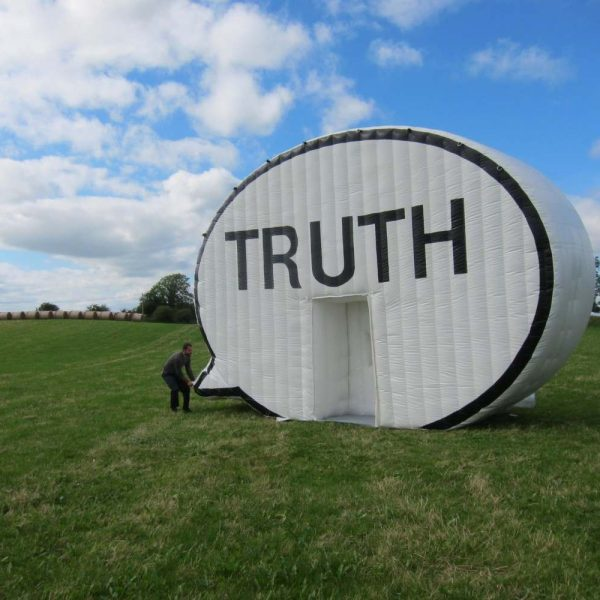 man lifting end of large inflatable speech bubble