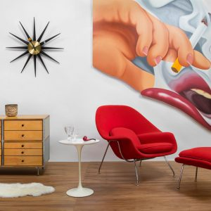 red chair and ottoman next to white table and large wall art