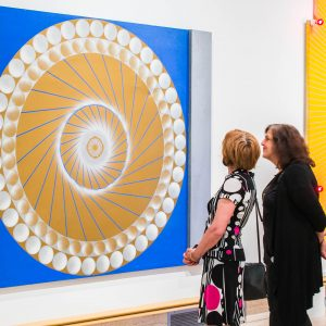 two women observing blue and yellow painting