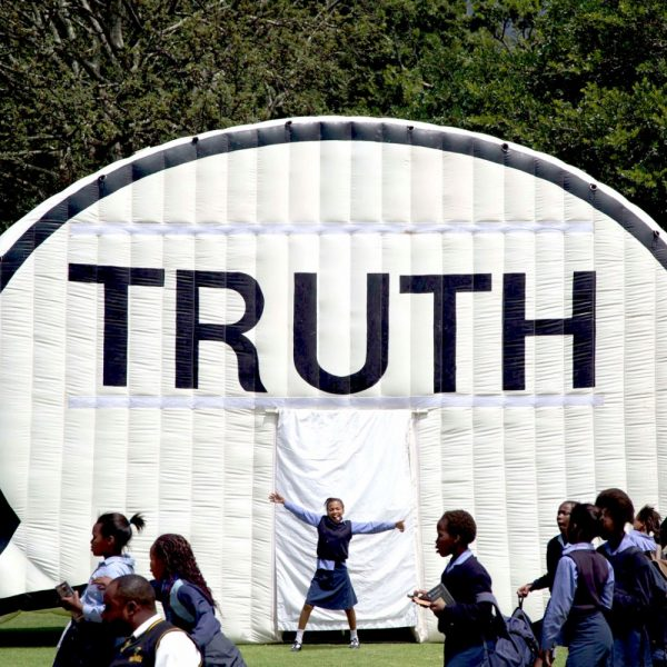 Female student poses next to Truth Booth inflatable speech bubble