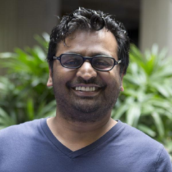 Patel headshot with blue v-neck shirt