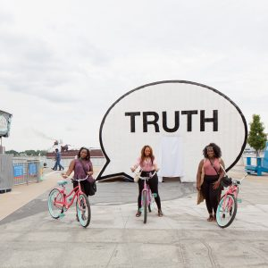 three girls with bikes stand next to Truth talk bubble