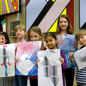 Children hold up their paintings