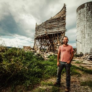 Scott Hocking stands in front of dilapidated wood structure