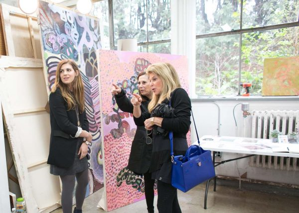 three women in jackets gesturing toward art