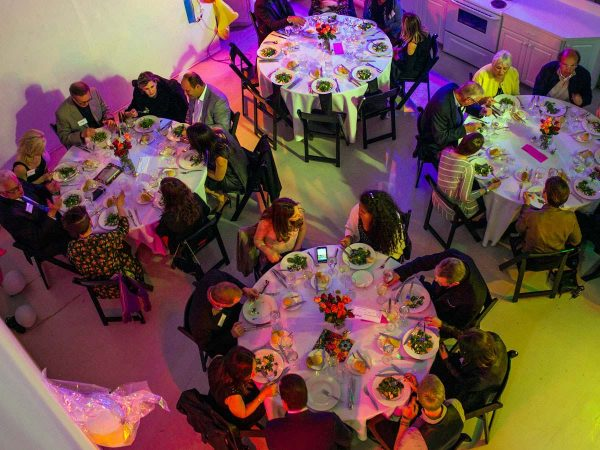 people sit at dining tables at dinner event