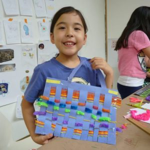 Create Camps, young girl shows off paper woven basket