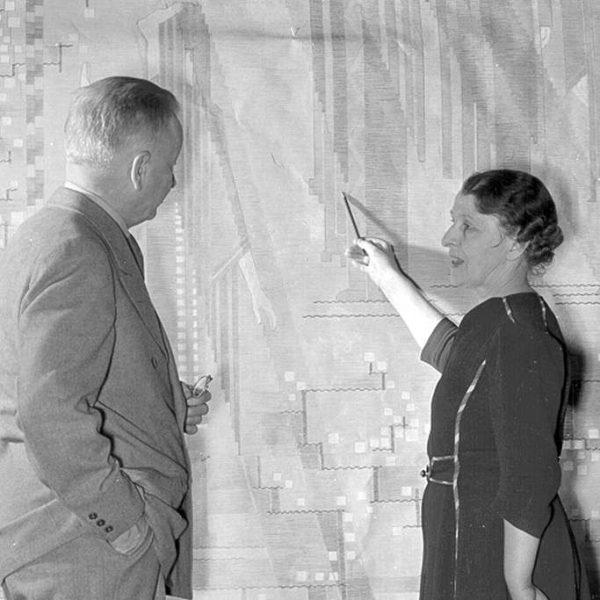Saarinens standing at tapestry