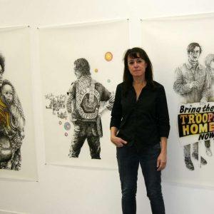 Deborah Aschheim posing with drawings of people