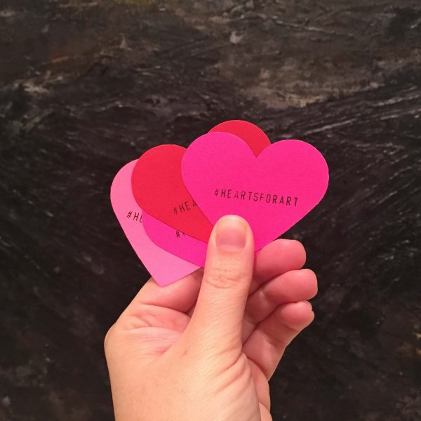 pink and red hearts held in a hand - Hearts for Art campaign