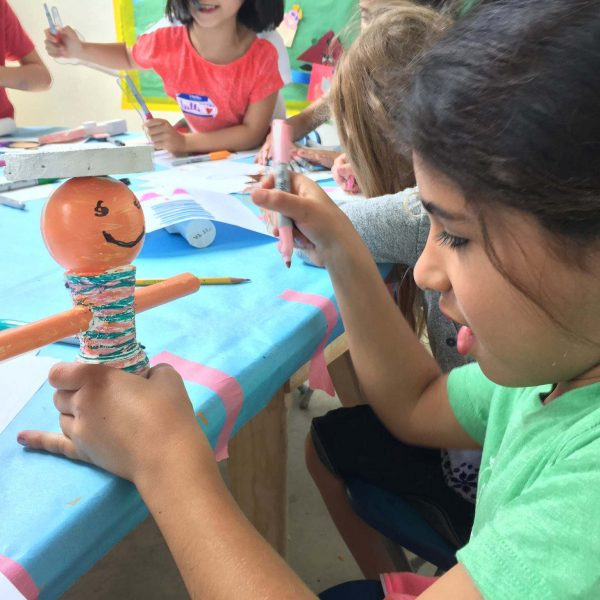 young girl in green t-shirt creates smiley figurine