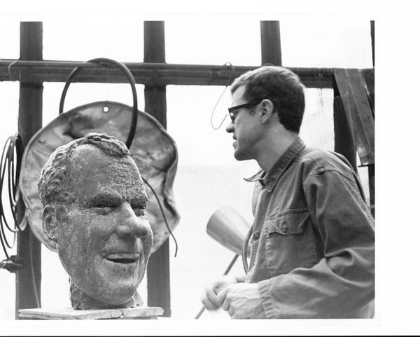 Fred Woell carving head from stone