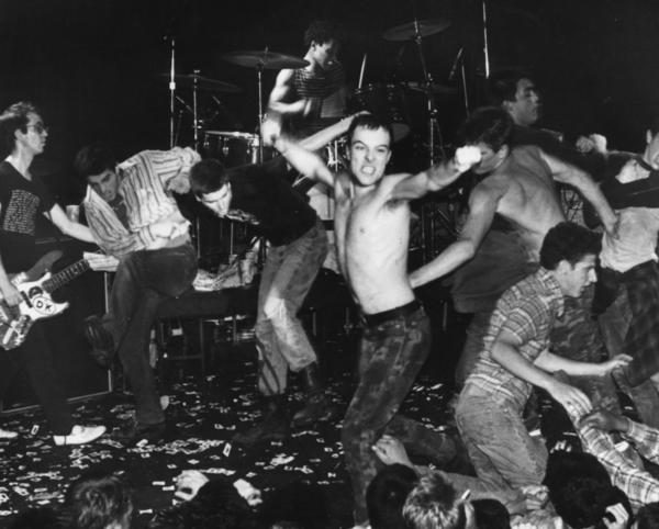 punk band performing on stage and removing clothing