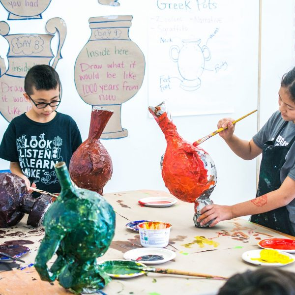 Children painting paper mache pottery