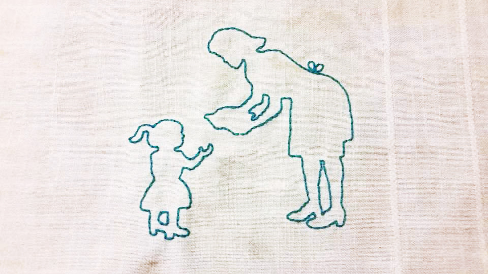 silhouette of woman and child stitched into fabric