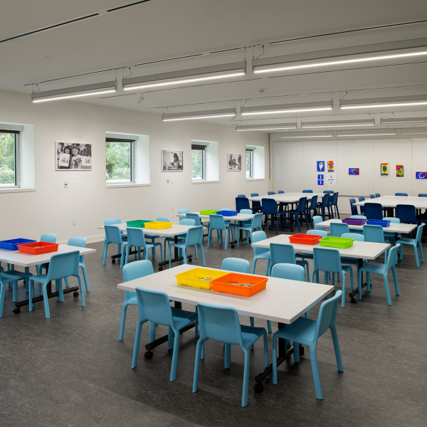 children's classroom with blue chairs and white tables