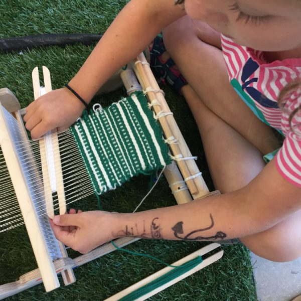 Child using small loom with green and white yarn