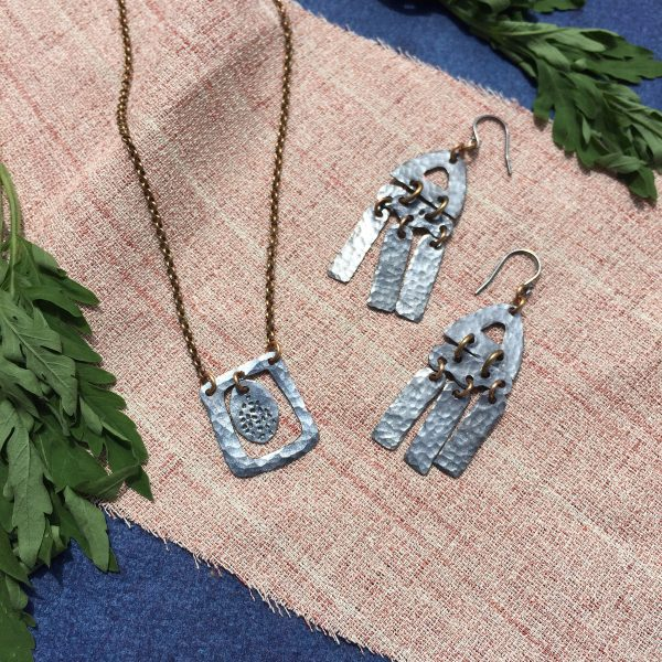 metal jewelry earrings and necklace on burlap