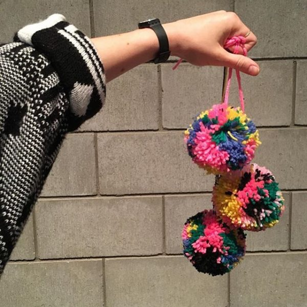 three yarn balls with pink string held up by hand