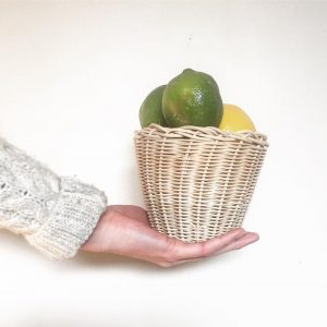 woven basket filled with fruit sits on hand