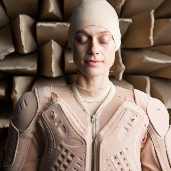 Lucy McRae headshot in flesh-toned armor