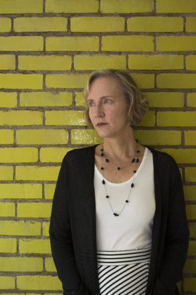 Deborah Kawsky stands in front of yellow brick wall