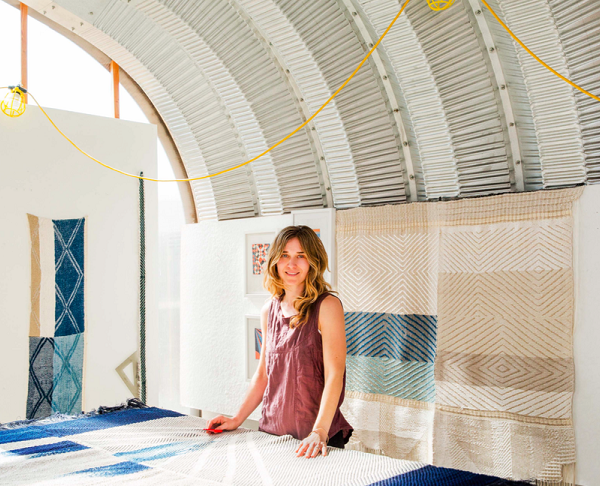 Christy Matson stands in front of blue and brown fabrics