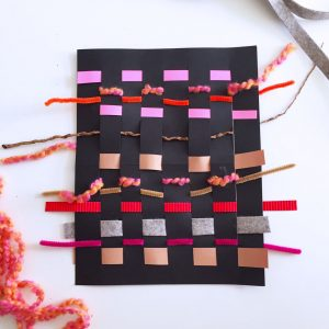 Finished paperweaving. Black base paper with colorful strips woven into it.