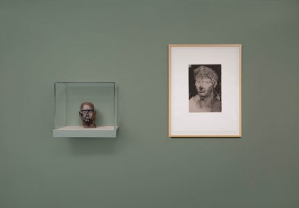 Small bust in glass case and print of bust-like portrait on muted green wall