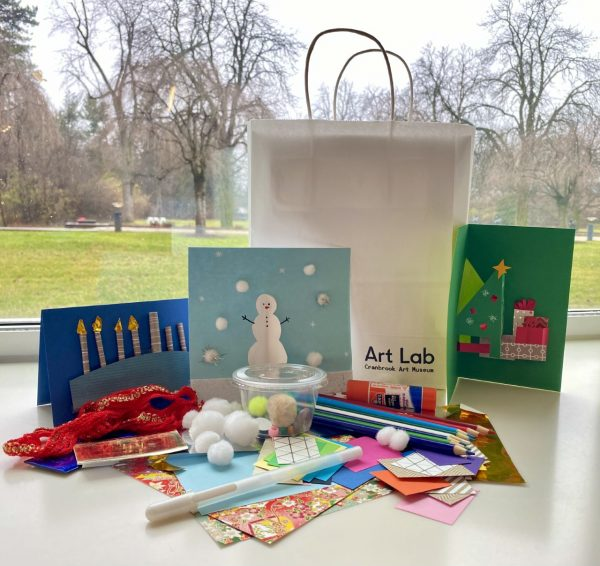 Various supplies for kids to make holiday cards with white bag labeled Art Lab