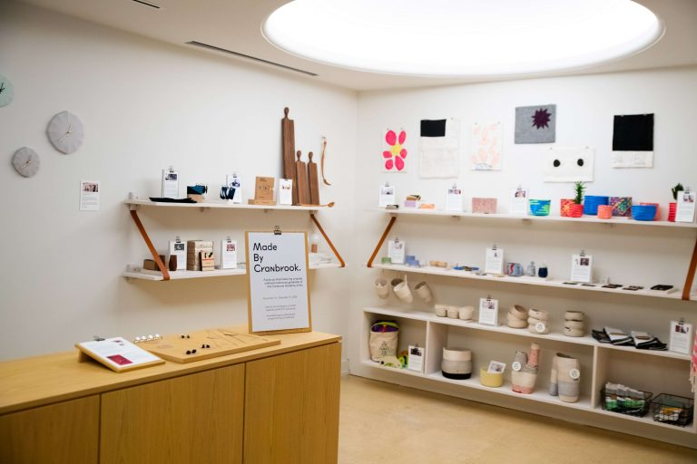 Wide angle view of handmade pop-up shop. Several shelves filled with objects on a white wall with overhead light.