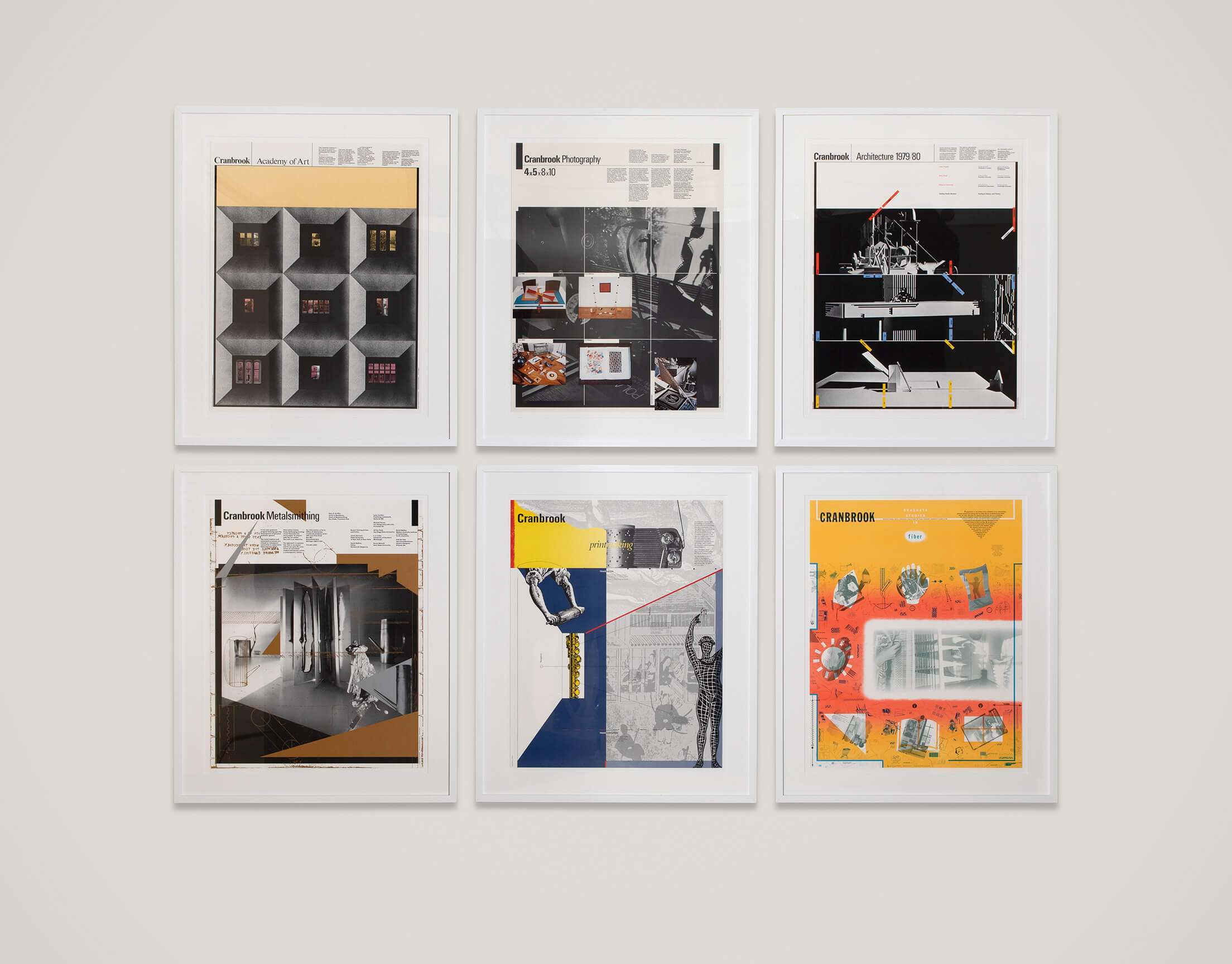 six posters arranged in white frames on white wall in two rows of three. Posters promote programs and Cranbrook Academy of Art.